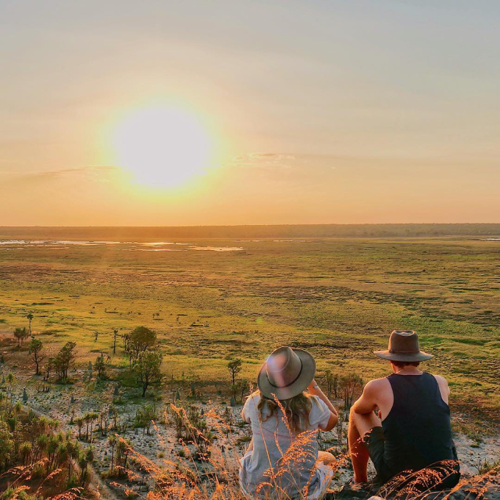 Two people look out across flood plains at sunset.