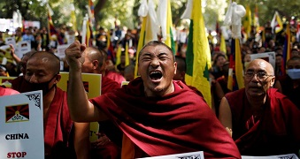 Monks wrapped in red robes hold flags and fists in the air, one man closes his eyes, yelling.