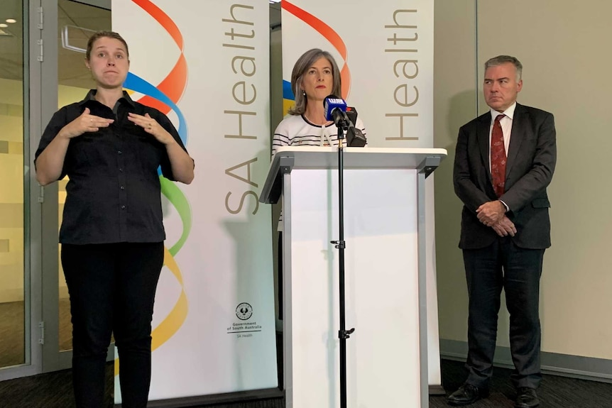 A woman stands at a podium with a woman on one side and a man on the right