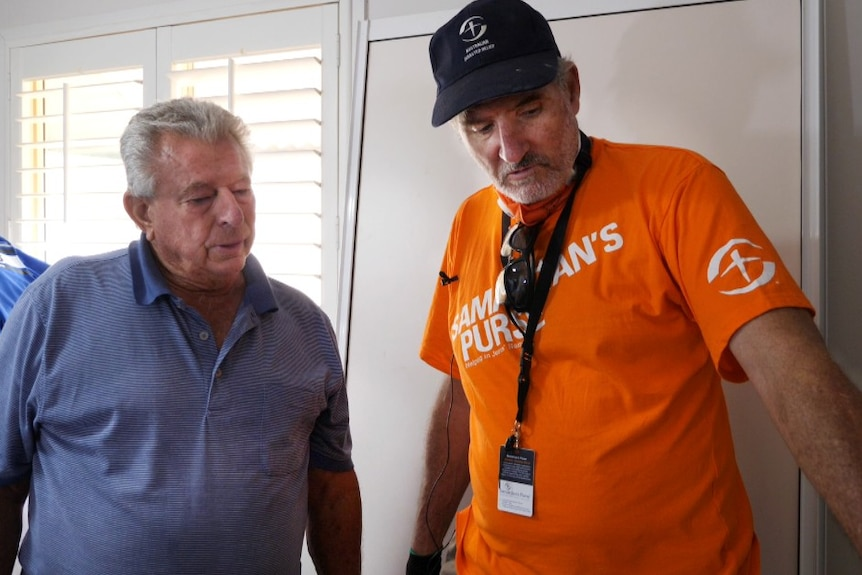 Two men stand looking at floor, inside a white room with slat blinds, younger man in orange volunteer T-shirt and cap