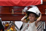 A young girl wearing a helmet in front of a funeral casket.