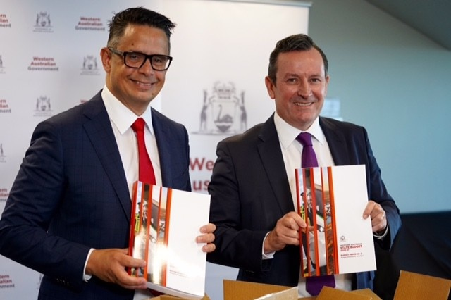 Ben Wyatt and Mark McGowan wearing broad grins and holding budget documents.