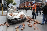 A car is flattened by bricks and rocks.