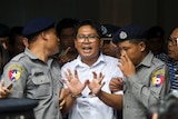 Reuters journalist Wa Lone talks to journalists as he is escorted by police