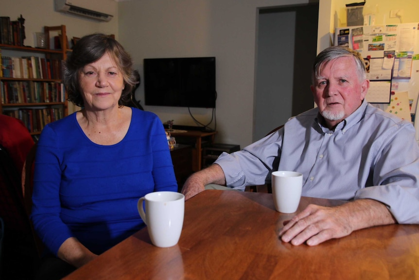 Julie and John Feary sit at a table in their Bateman granny flat.