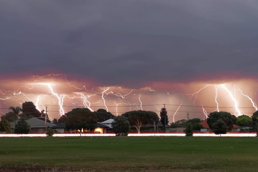 Multiple lightning strikes over an oval and houses
