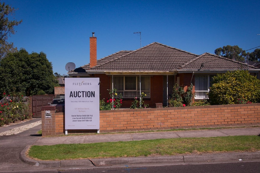A red brick home with a sign out the front saying 'auction'.