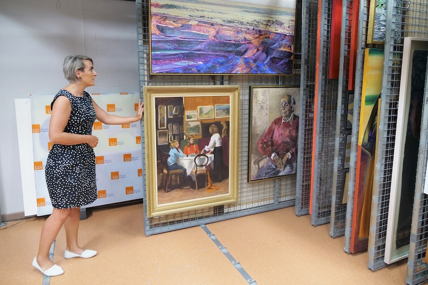 A woman pushing a sliding rack of artwork in a store room, colourful 2D artworks on display.