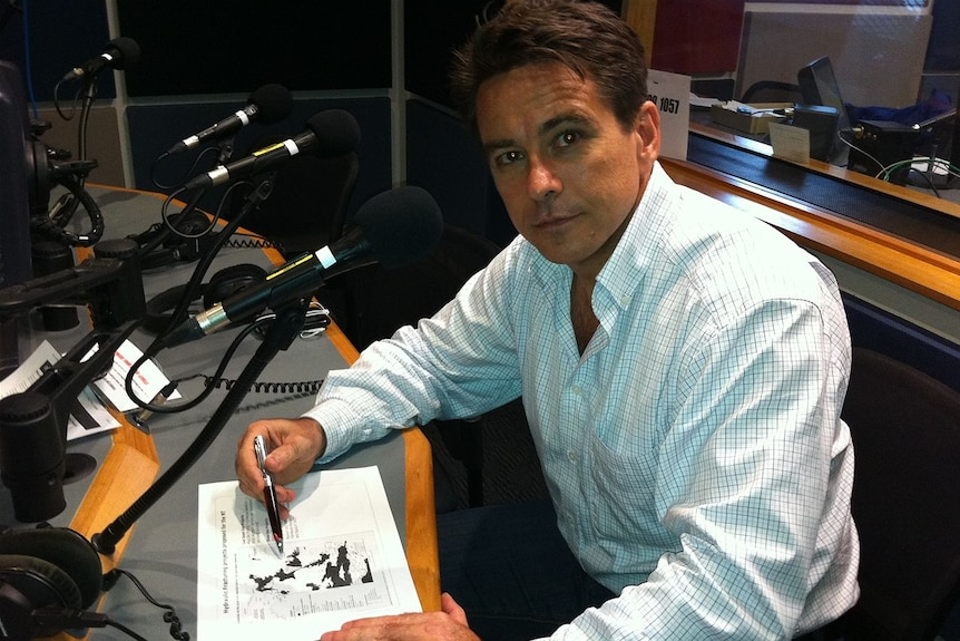 Man in a radio studio looking at camera with a a map laid before him.