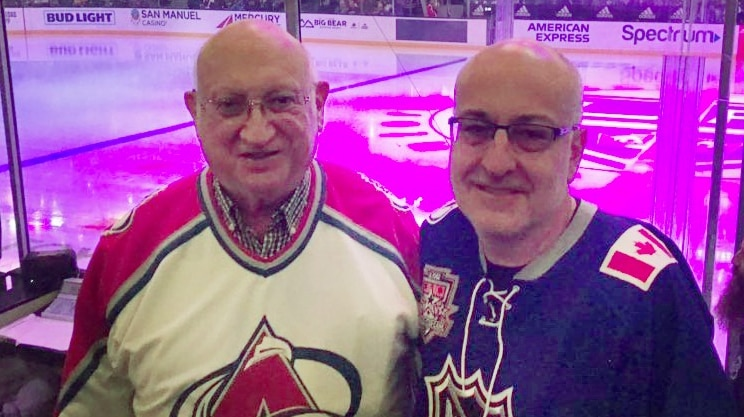 Two men stand arm in arm, and smile at the camera with an ice hockey field behind them.