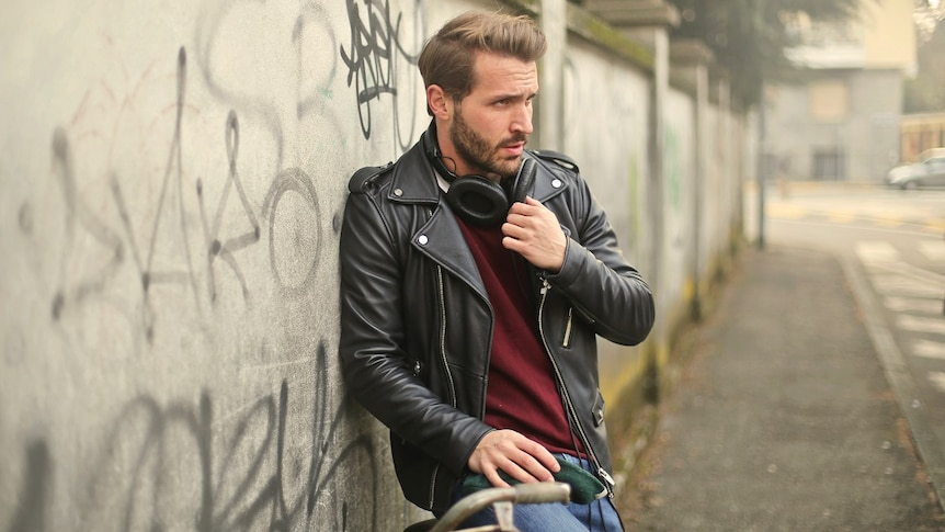 Man wearing a leather jacket over a maroon jumper leaning against a wall in a street, a classic casual men's clothing item.