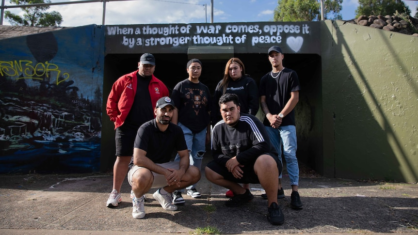 Members of Manifold standing in front of overpass walkway, which has a Baha'i quote about peace painted on it.