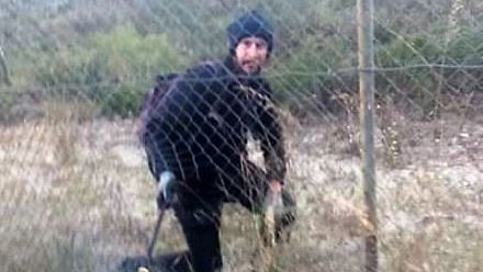 A man dressed in black climbing through a hole in a cyclone wire fence.