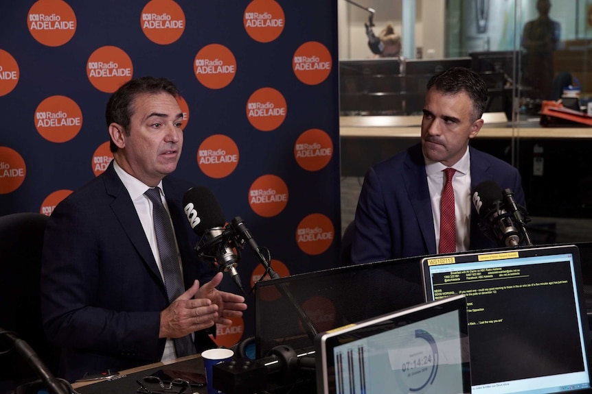 Two men in a radio booth with one one man speaking while the other looks at him.