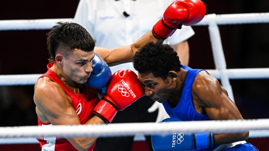Man in red singlet punches man in blue singlet in boxing match