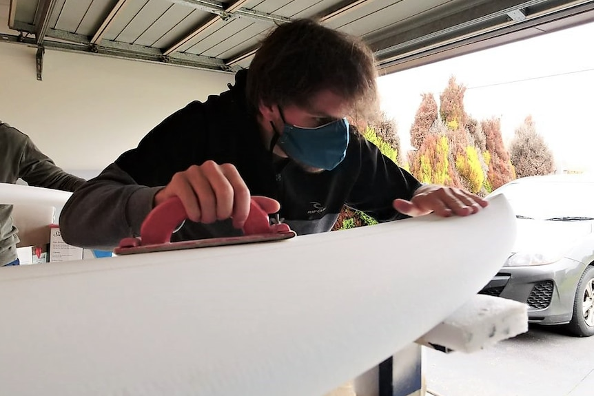 A man wearing a facemask uses a sander to shape a white surfboard in a garage.