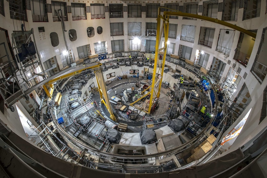 Inside an enormous cavity at the ITER site several stories high a number of people work amid scaffolding on the site.