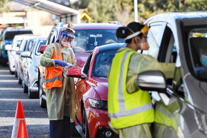 A woman in a hi-vis vest talks to the driver of a car in a long line of cars