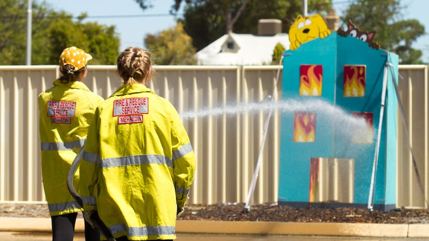 Two women wearing yellow hi-vis hold a hose spraying water at a fake blue cutout building