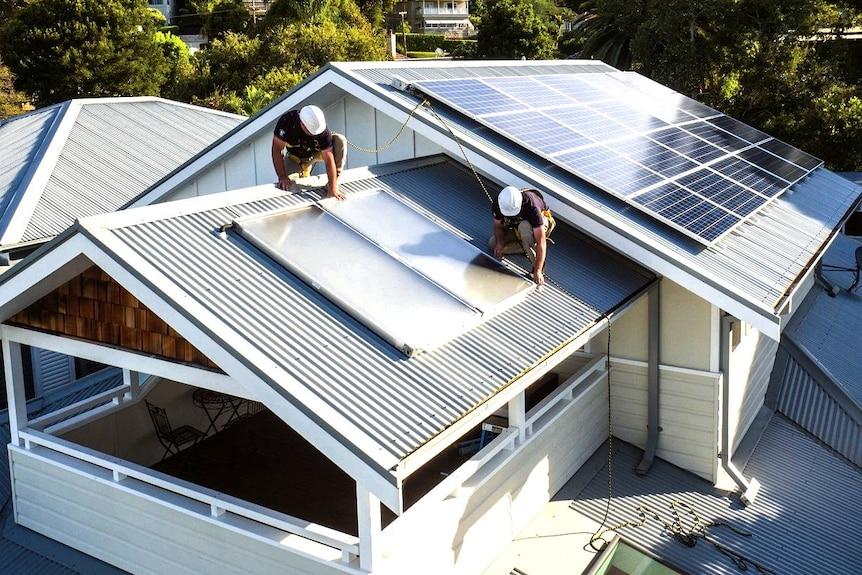工人在房子的屋顶上安装太阳能。