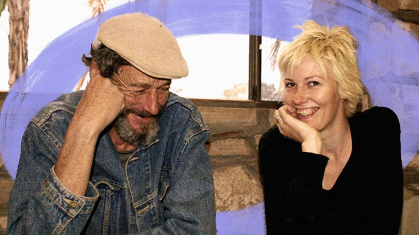 A man smiles while looking down. A young woman sits next to him smiling towards the camera.