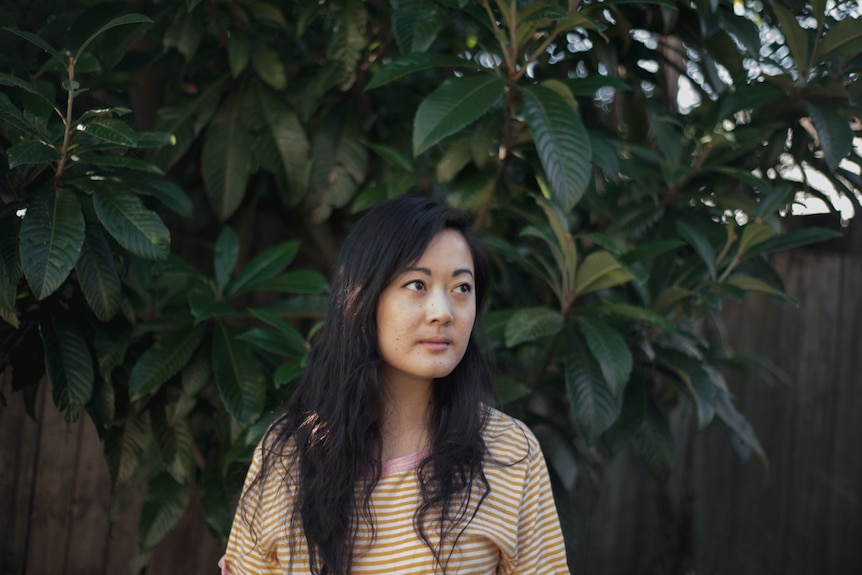 The novelist Jessie Tu standing in front of a plant out in the sunshine