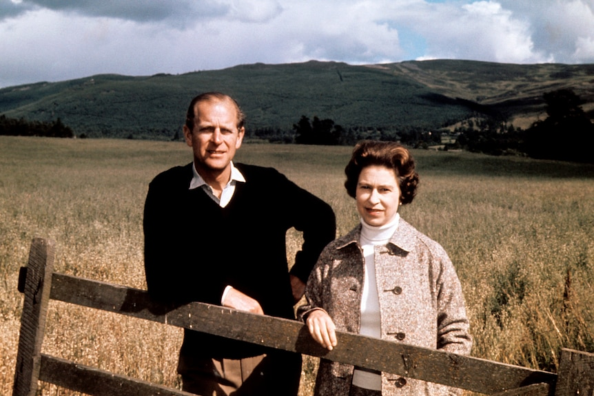 A man and a woman stand at a fence in the Scottish countryside.