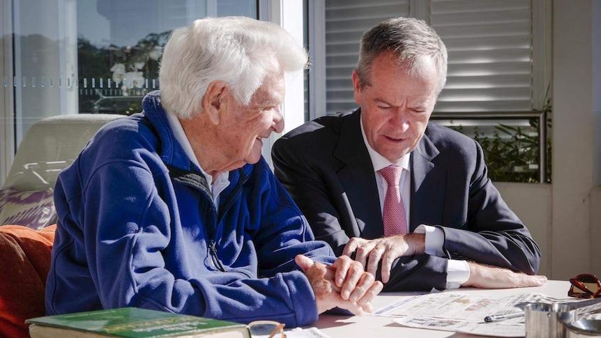 Bob Hawke, left, wearing a purple jumper, and Bill Shorten, wearing a suit, scrutinise the newspaper