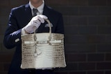 a crocodile skin handbag being held by a man in a suit and white gloves.