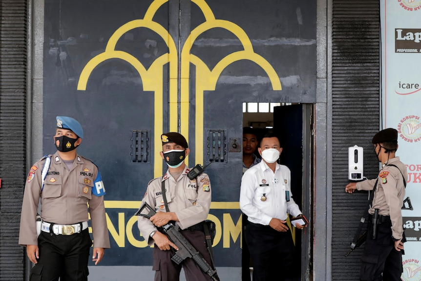Four uniformed security guards in face masks stand guard in front of grey modern building
