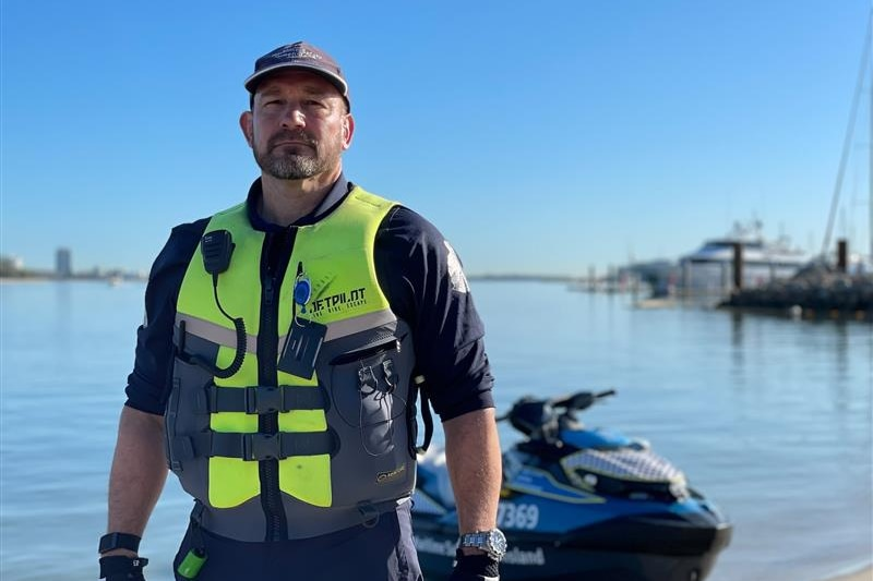 A man in maritime authority uniform at a marina