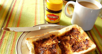 A table setting is seen with a cup of coffee, jar of vegemite and vegemite toast.