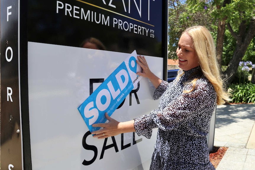 "Real estate agent Chelsey Grant next to a ""For Sale"" sign placing a blue ""SOLD"" sticker over the top of it."