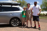 Siobhan Toohill standing with her family beside their car in front of the Windorah Pub in south-west Queensland.