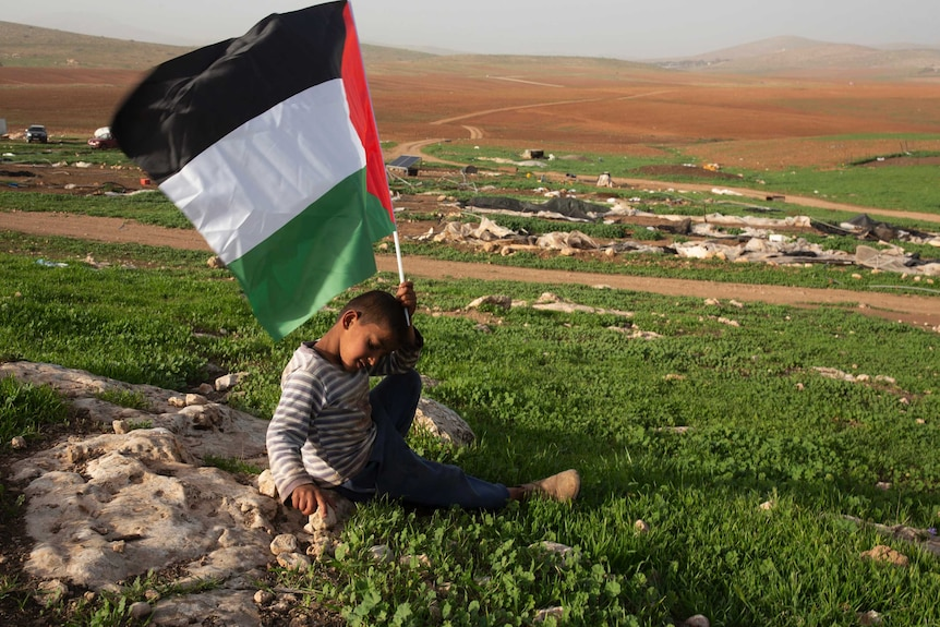 A Palestinian Bedouin boy holds a Palestinian flag in front of rubble