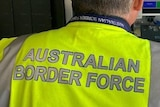 Unidentified Australian Border Force worker seen from behind, at airport security.