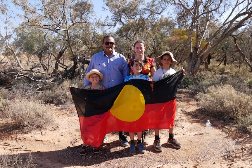 A man, a woman and three children smile at the camera, the children hold and Aboriginal flag.