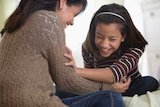A mother and daughter laugh together while sitting on a bed.