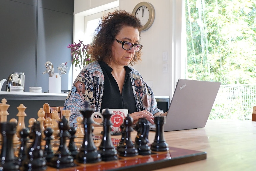 Sonya Meredith types on her laptop at her home in Toowong in Brisbane