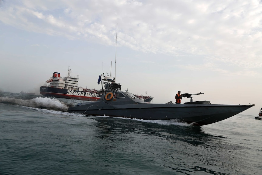 An Iranian speedboat with a machine gunner on the front moves around a British-flagged oil tanker.