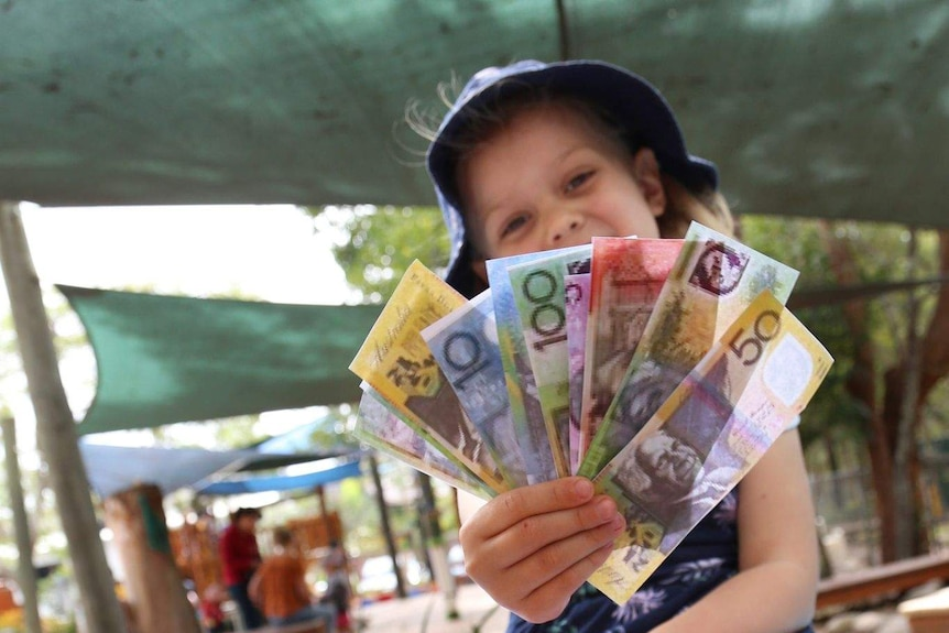 A young girl sits on a boat in a playground, holding pretend money. She is smiling.