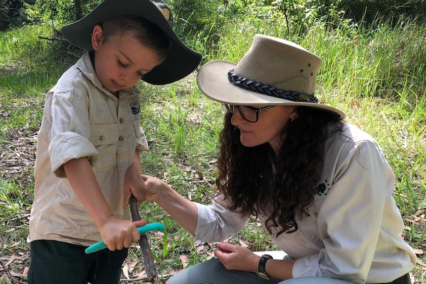 A boy cuts a stick in the bush while a teacher observes.