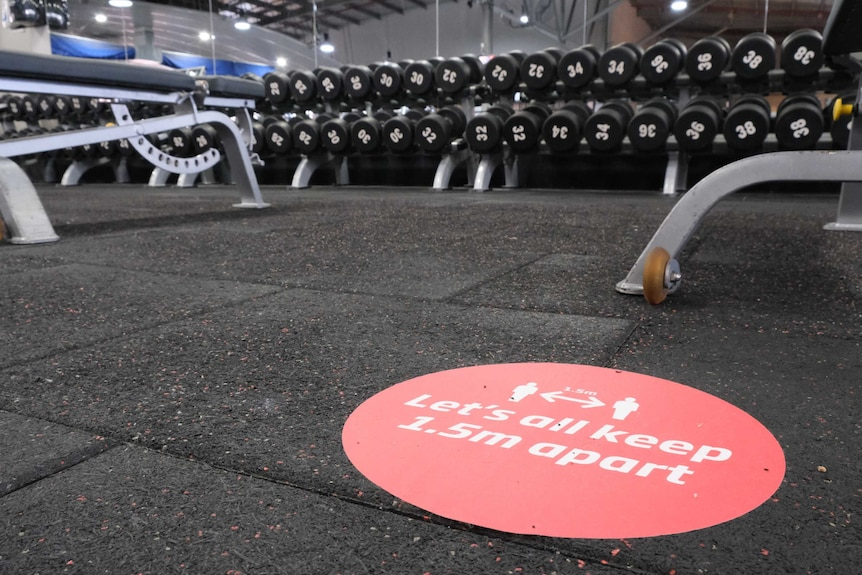 A sticker on the floor reminds patrons to socially distance at a gym, with weights in the background.