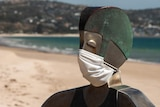 A metal sculpture of a lifeguard wearing a face mask in front of an empty beach