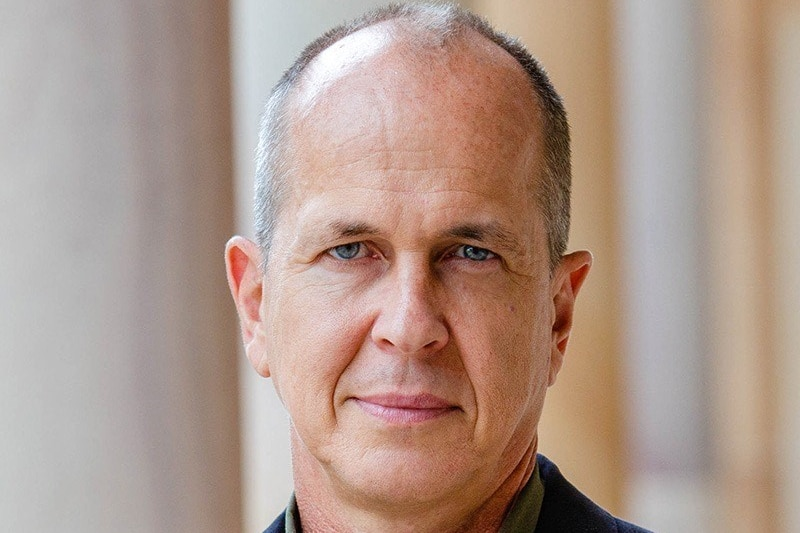 A profile photo of Peter Greste wearing a blue coat and green shirt.