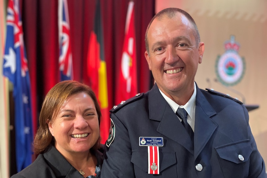 A man in his firefighter's uniform at a bravery awards ceremony with his wife