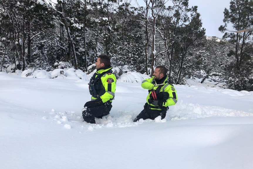 Two police officers walking through deep snow