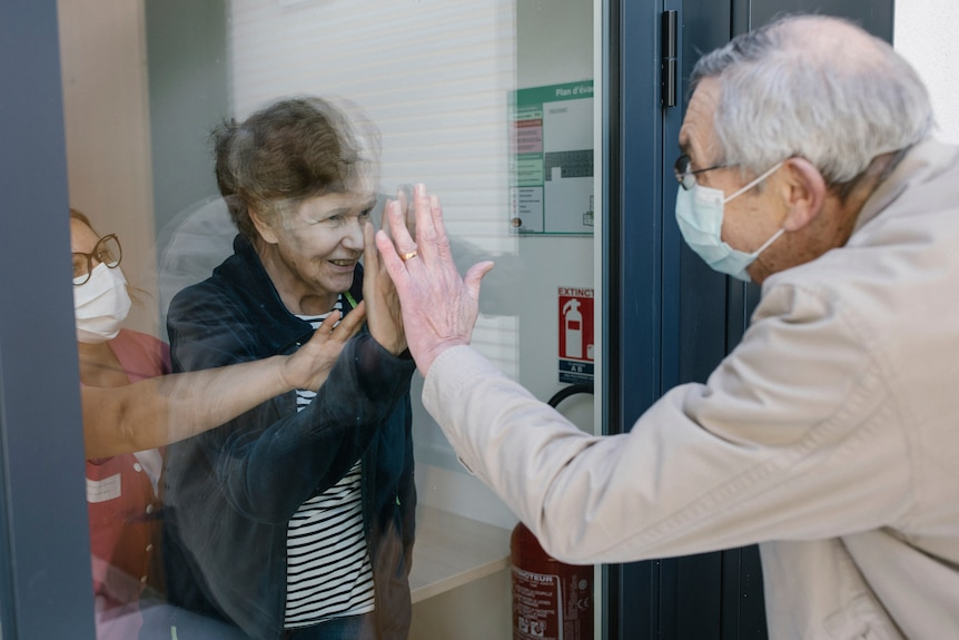 An elderly man and woman hold their hands together through a glass window.