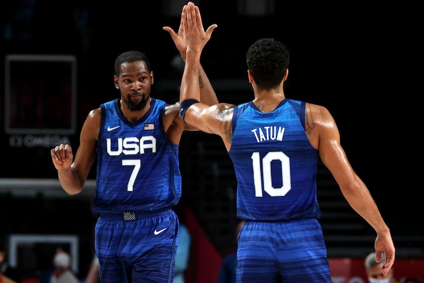 Kevin Durant and Jayson Tatum of Team USA basketball exchange a high five.