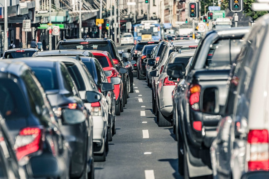 Gridlock traffic on a busy Sydney road during peak hour. The camera's perspective looks between two lanes of stationary cars.